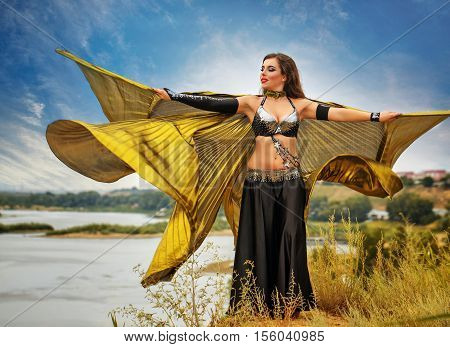 Oriental Beauty dance with wings. Nice girl in national dress dancing in the open air. Nomads. Beauty and elegance