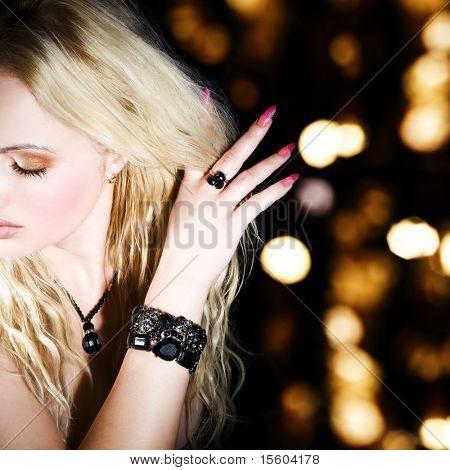 Женщина с ювелирными изделиями на сверкающих фоне