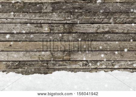 Pile of snow with old wooden planks background. Free space for text