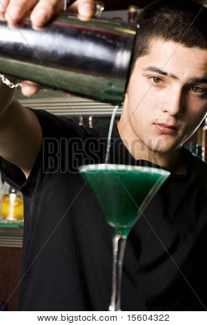 Barman with shaker making cocktail. Focus on face