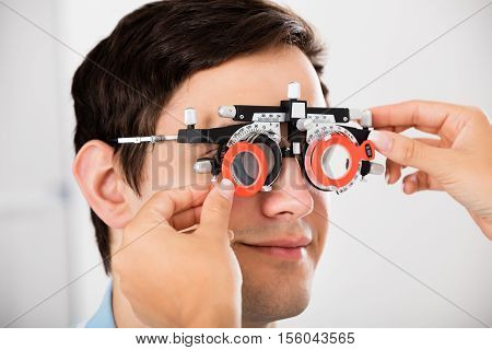 Close-up Of An Optometrist Checking Male Patient Vision With Trial Frame At Eye Clinic