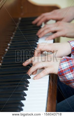 Close Up Of Boy Playing Piano Duet With Teacher