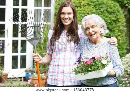 Portrait Of Teenage Granddaughter Helping Grandmother In Garden