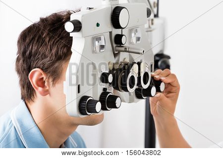 Close-up Of An Optometrist's Hand Adjusting Phoropter For Young Male Patient