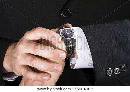 Businessman checking the time on his wrist watch poster