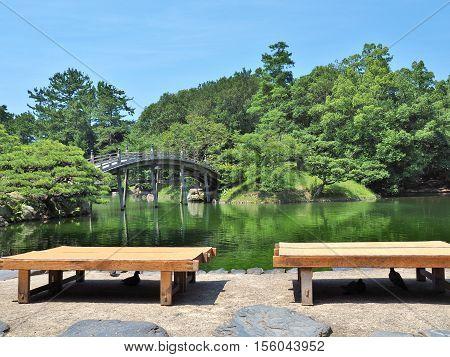 Wooden benches and wooden bridge - Engetsukyo in Ritsurin Garden in Takamatsu city, Kagawa Prefecture, Japan. Ritsurin Garden is one of the most famous historical gardens in Japan.