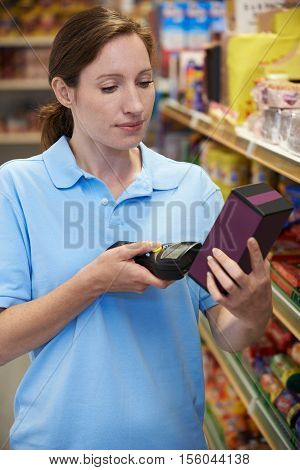 Sales Assistant Checking Stock Levels In Supmarket Using Hand Held Device