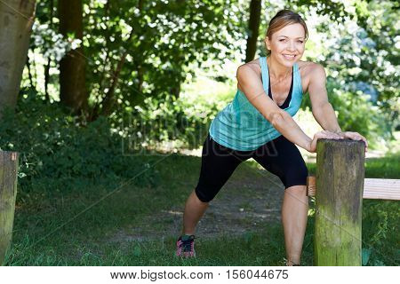 Mature Woman Warming Up Before Exercising In Countryside