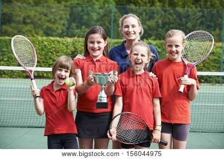 Portrait Of Victorious School Tennis Team With Trophy