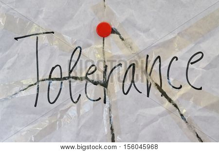 Word Tolerance written on torn background with red pin
