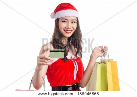 Smiling woman holding shopping bags before christmas showing credit card. Focus on card.