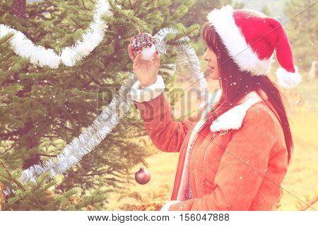 Beautful girl decorating her Christmas tree outdoor