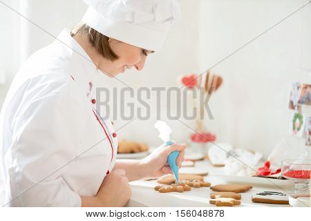 Professional smiling female confectioner decorating a gingerman with icing sugar using a pastry bag, preparing for Christmas. Lifestyle, horizontal, Christmas concept photo