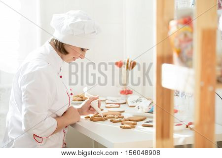 Professional female confectioner sitting and decorating a gingerman with icing sugar using a pastry bag, preparing for Christmas. Lifestyle, Christmas concept photo