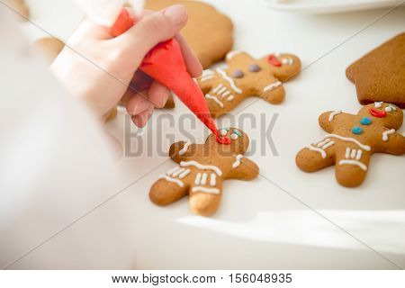 Close up of confectioner hand decorating a gingerman with a pastry bag, drawing a smile, making it cute, fun and delicious View over a shoulder, lifestyle
