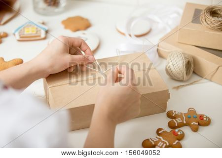 Close up of confectioner hands wrapping a simple kraft cardboard box. Christmas concept photo, lifestyle