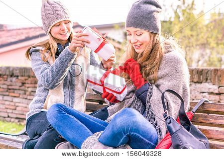 Happy girlfriends in winter clothing holding gifts box outdoors at city park - Young sisters opening presents sitting on urban bench with smiling face - Love and teenage friendship concept