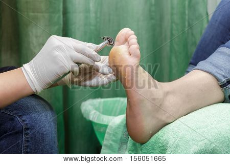 Pedicure  procedure in the beauty salon.  emover calluses on the feet. Foot care.