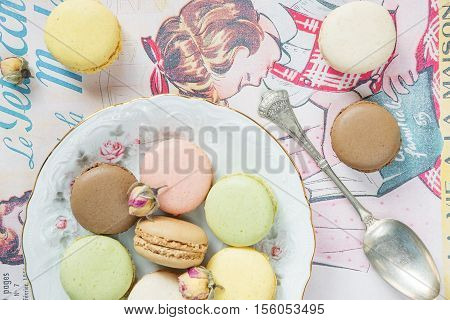 Multicoloured almond cookies (macaroons) on beautiful porcelain plat on vintage magazine; top view flat lay composition