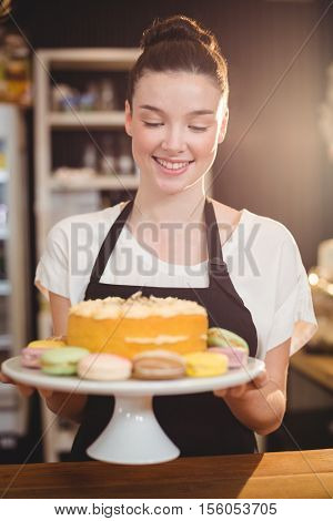 Smiling waitress holding dessert on cake stand in cafe