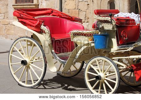 An old style horse driven carriage waiting for a customer