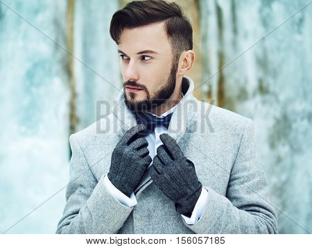 Outdoor portrait of handsome man in gray coat. Fashion photo. Beauty winter style