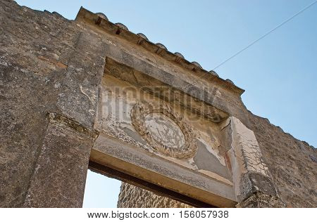 The relief of laurel wreath on the gate at the entrance to ancient Roman villa Pompeii Italy.