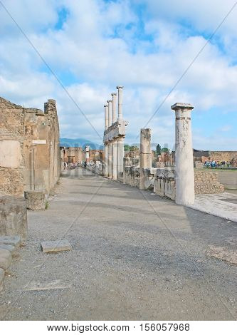 The walk along the ruined Pompeii street with the stone and brick walls of ancient villas and slender columns of Roman Temples Italy.