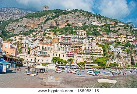 POSITANO ITALY - OCTOBER 5 2012: The fishing boats on the sand of Marina Grande adjacent to the colorful cottages and villas cafes and taverns on the and the huge medieval Cathedral of Santa Maria Assunta on October 5 in Positano.