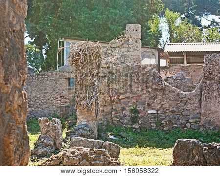 The walk among the stone ruins of the ancient buildings of Pompeii Italy.