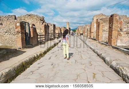 POMPEII ITALY - OCTOBER 4 2012: The wide street of ancient town with preserved paiving stone and walls of buildings on October 4 in Pompeii.
