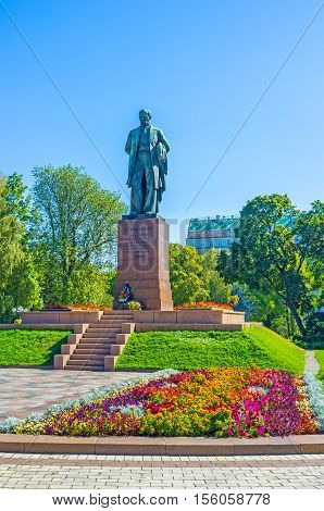 The monument of Taras Shevchenko the most famous Ukrainian poet writer and painter surrounded by colorful flowers and lush trees of park Kiev Ukraine.