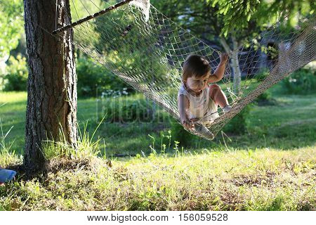 small child playing outdoors in a wicker rocking hammock in the country