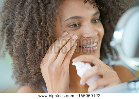 Portrait of beautiful mixed-race woman applying cosmetics on her face