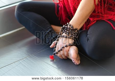 Young beautiful woman sitting in lotus pose with mala beads. Blurred yoga background. Concept for concentration or meditation.