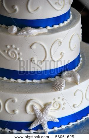Beautiful three-tier cake in blue and white, with seashore theme.