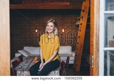 Portrait of an attractive young blonde woman smiling while sitting on a table her modern loft apartment