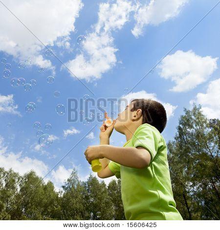 Menino soprando bolhas contra o céu azul