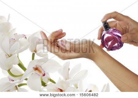 Mujer aplicar perfume en su muñeca. Orquídeas blancas sobre fondo