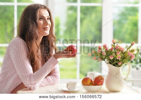 Happy young woman with fruits at home