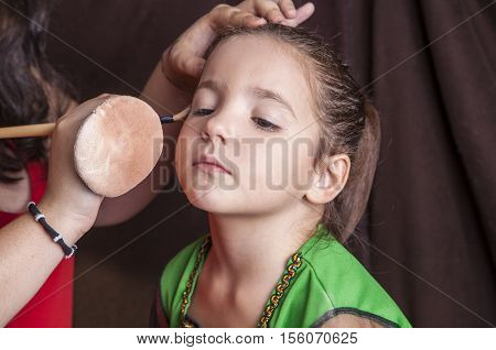 Little cute girl making facepaint before halloween party. The make-up artist is applying some foundation