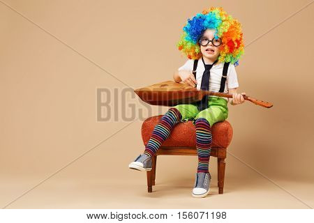 Blithesome Children. Happy Clown Boy In Large Neon Colored Wig Playing The Balalaika And Singing.