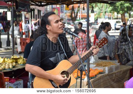 KUALA LUMPUR, MALAYSIA - DECEMBER 31, 2015 - Unidentified malaysian guy playing guitar and singing in the streets of Kuala Lumpur