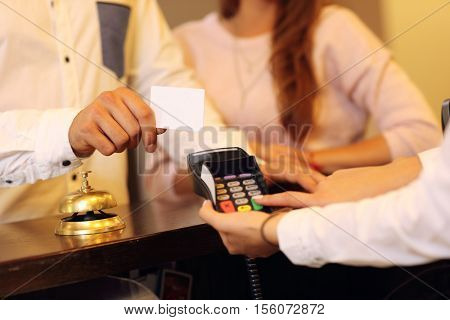 Midsection of couple at counter paying for hotel