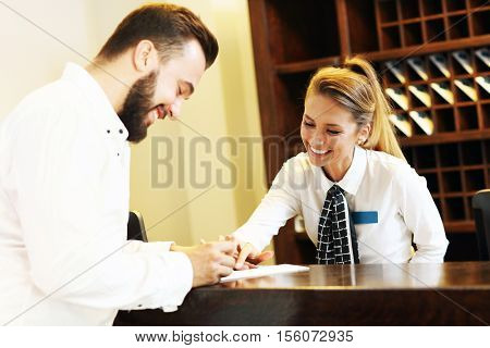 Picture of young businessman signing bill in hotel