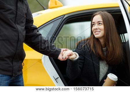 Man takes a womans hand to help get out of taxi. Portrait of smiling young business lady