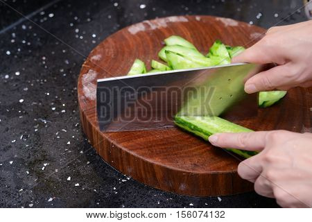 lady preparing cucumber slices on a wooden chop board