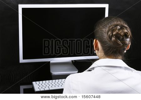Geschäftsfrau an ihrem Arbeitsplatz. Sie können Ihr Bild auf Computer-Monitor platzieren.