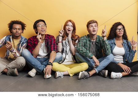 Multiethnic group of smiling young people sitting and pointing up over yellow background