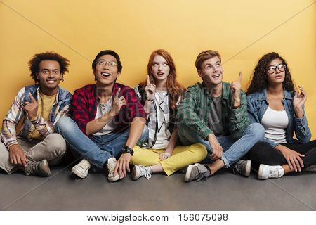 Multiethnic group of happy young people pointing up and having an idea over yellow background